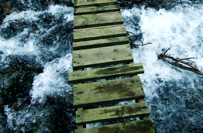 wooden footbridge over a raging torrent