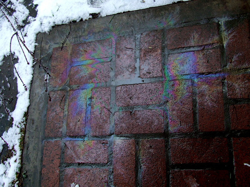 chainsaw oil-leak rainbows on bricks