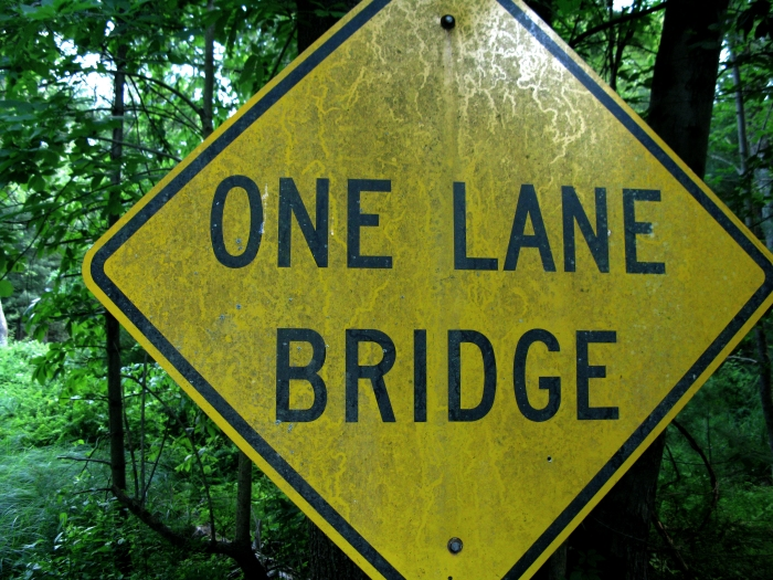 one lane bridge sign in the forest
