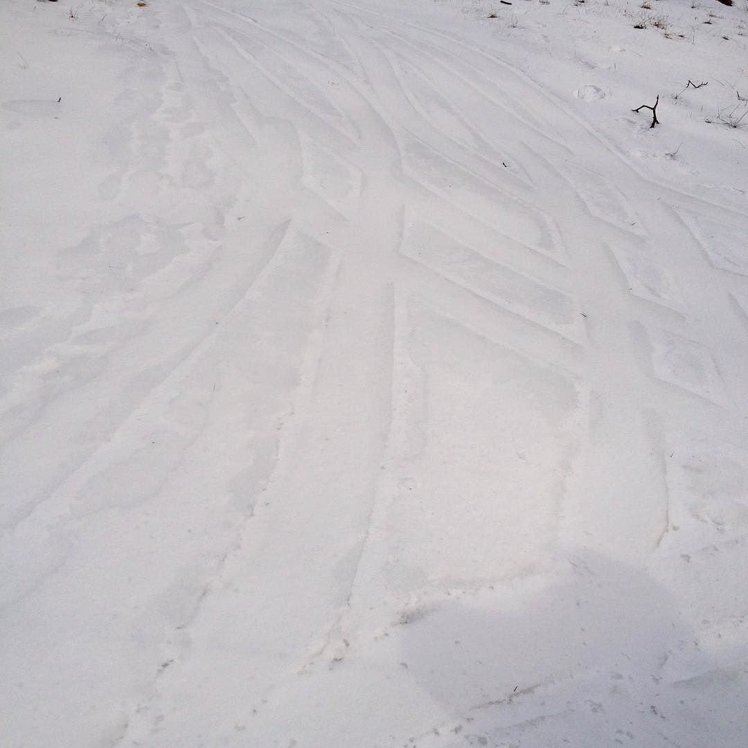 Interlaced pattern of tire tracks in the snow.