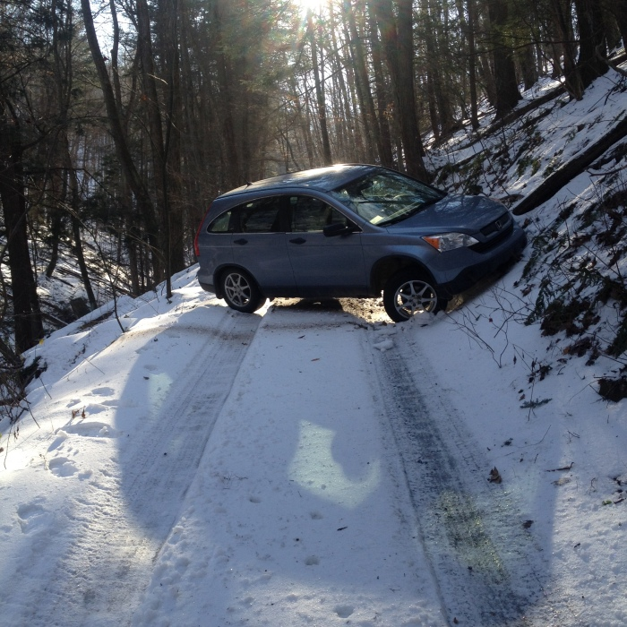 car turned sideways on a one-lane road through the woods