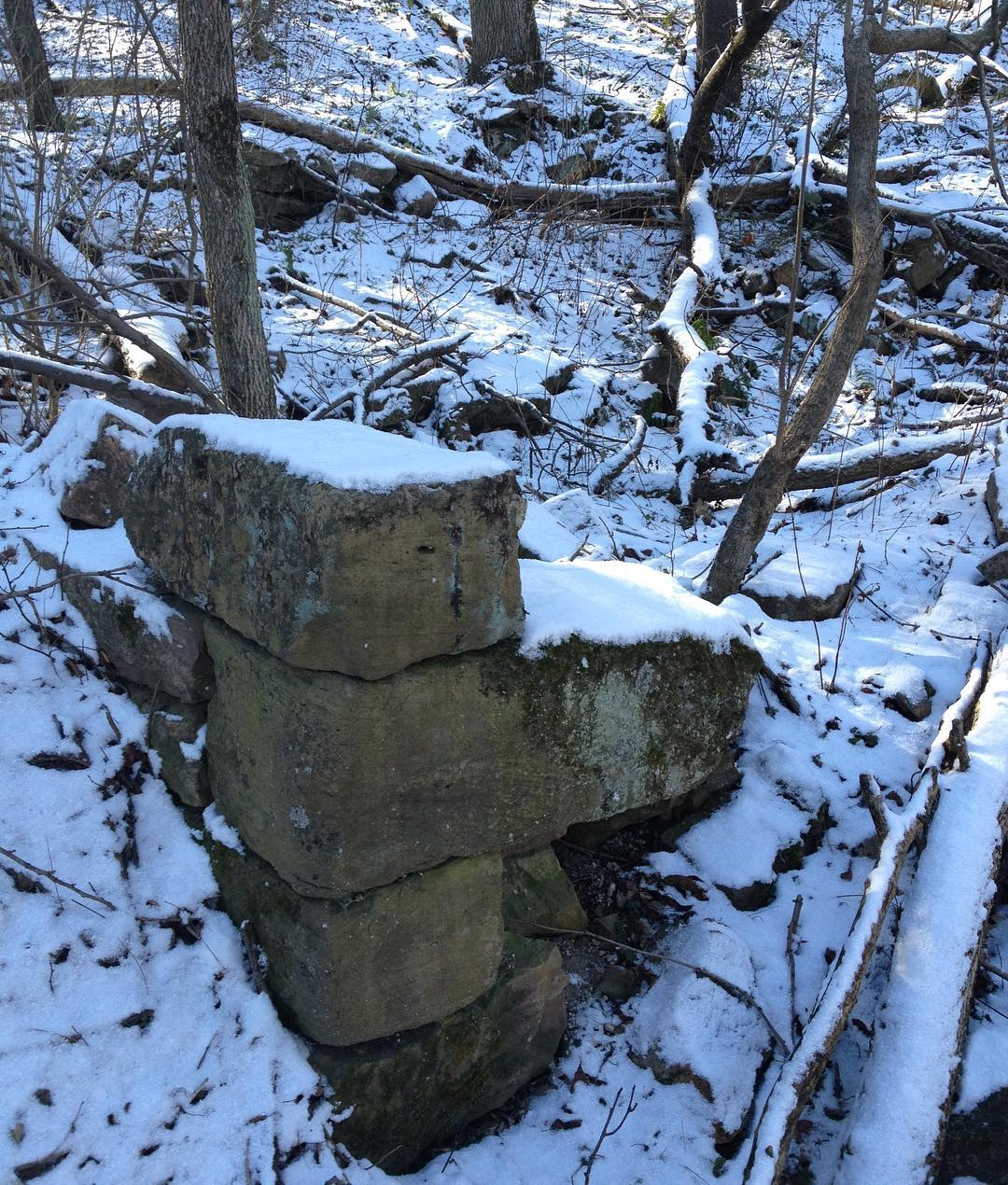The corner stones of an otherwise vanished house in the woods, dusted with snow.