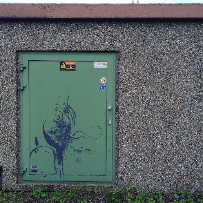 Enigmatic street art on an electric substation door.