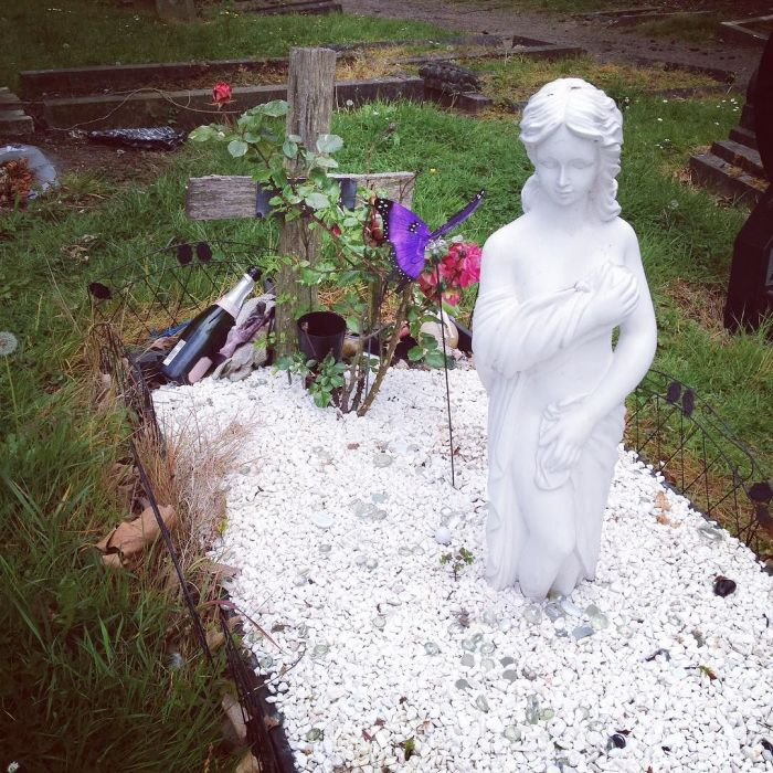 A grave plot with a statue of a nearly naked woman and a bottle of champagne next to the cross.