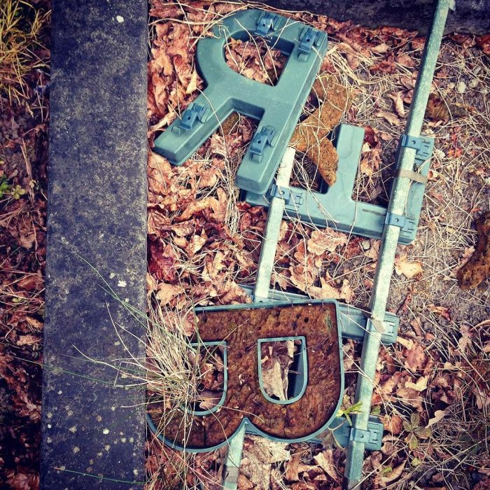 Discarded plastic letters (R, E and B) from temporary graveyard memorial displays.