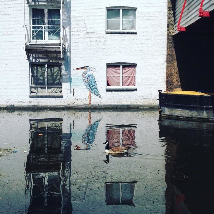 Painting of a heron above the waterline on the side of a building next to the water, with a Canada goose about to cross its reflection.