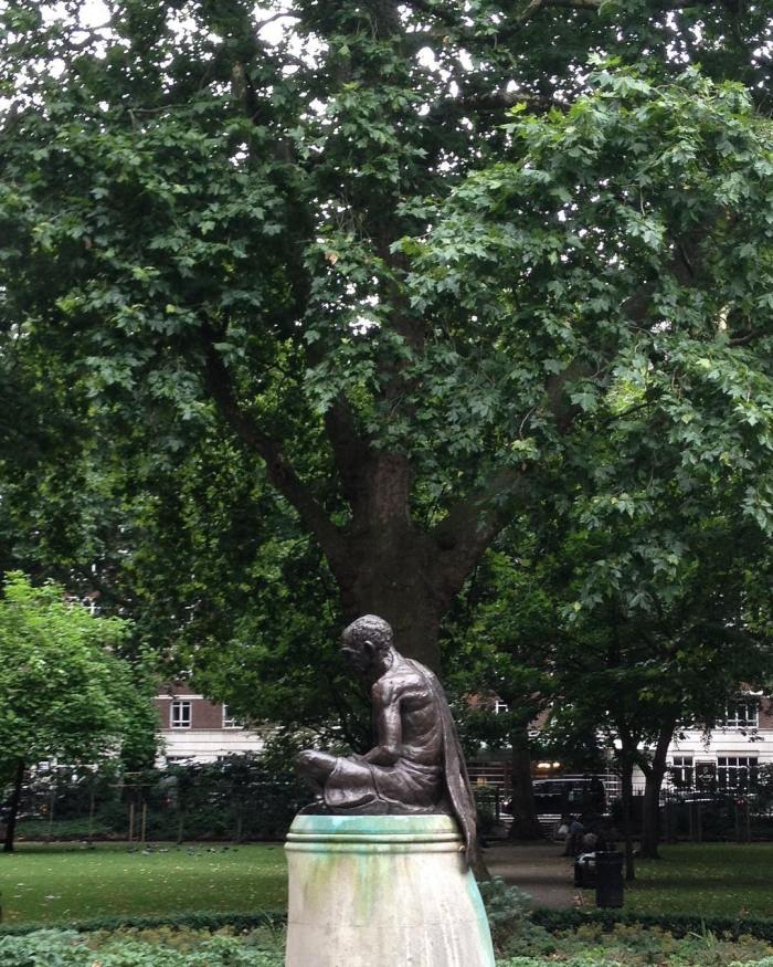 Sideways view of the Gandhi memorial in London with a big tree in the background.