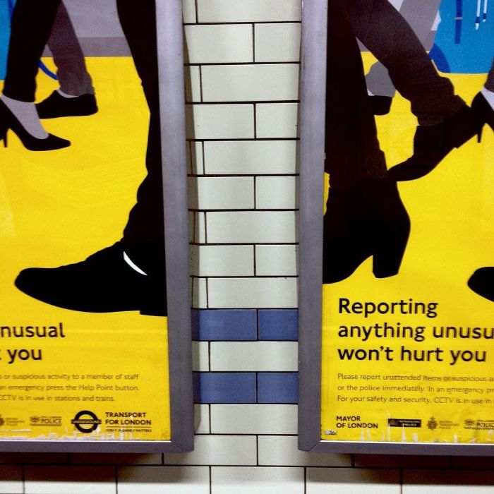Two identical signs, with a gap between them, showing a graphic of walking feet and urging people to report anything unusual.