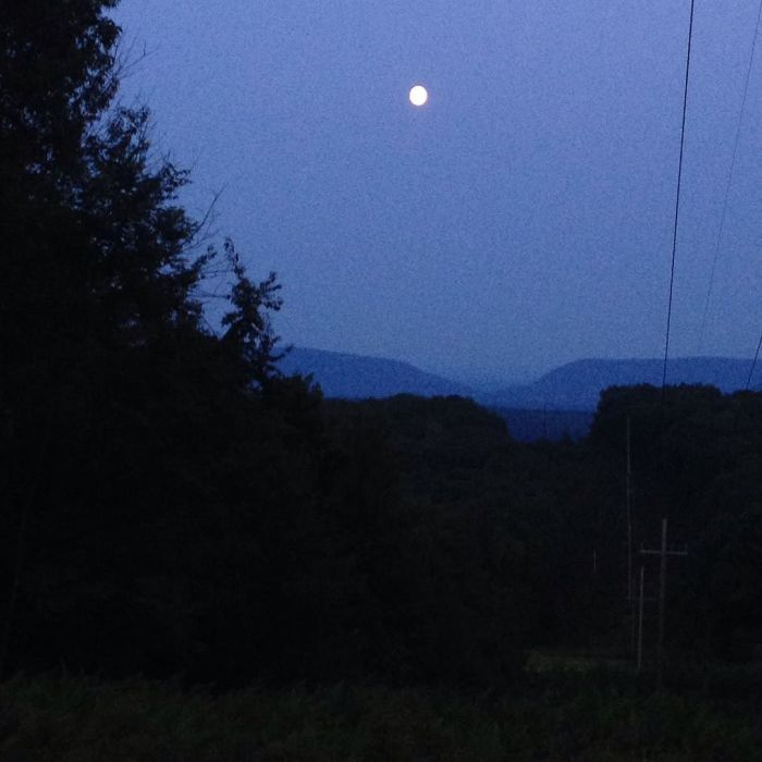 Full moon rising over wooded ridges.