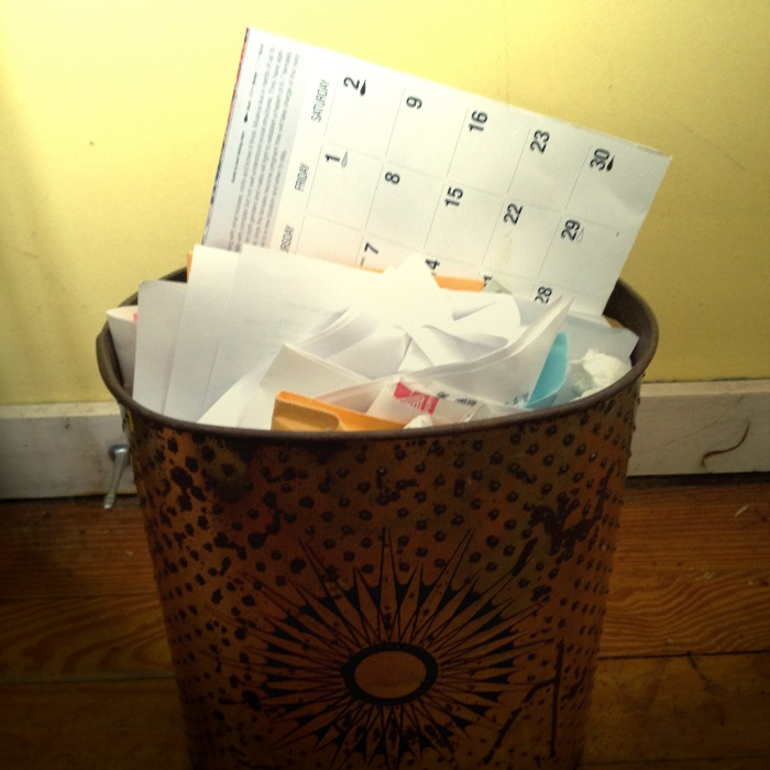 a wall calendar in a metal trash can with a solar design on the side of it