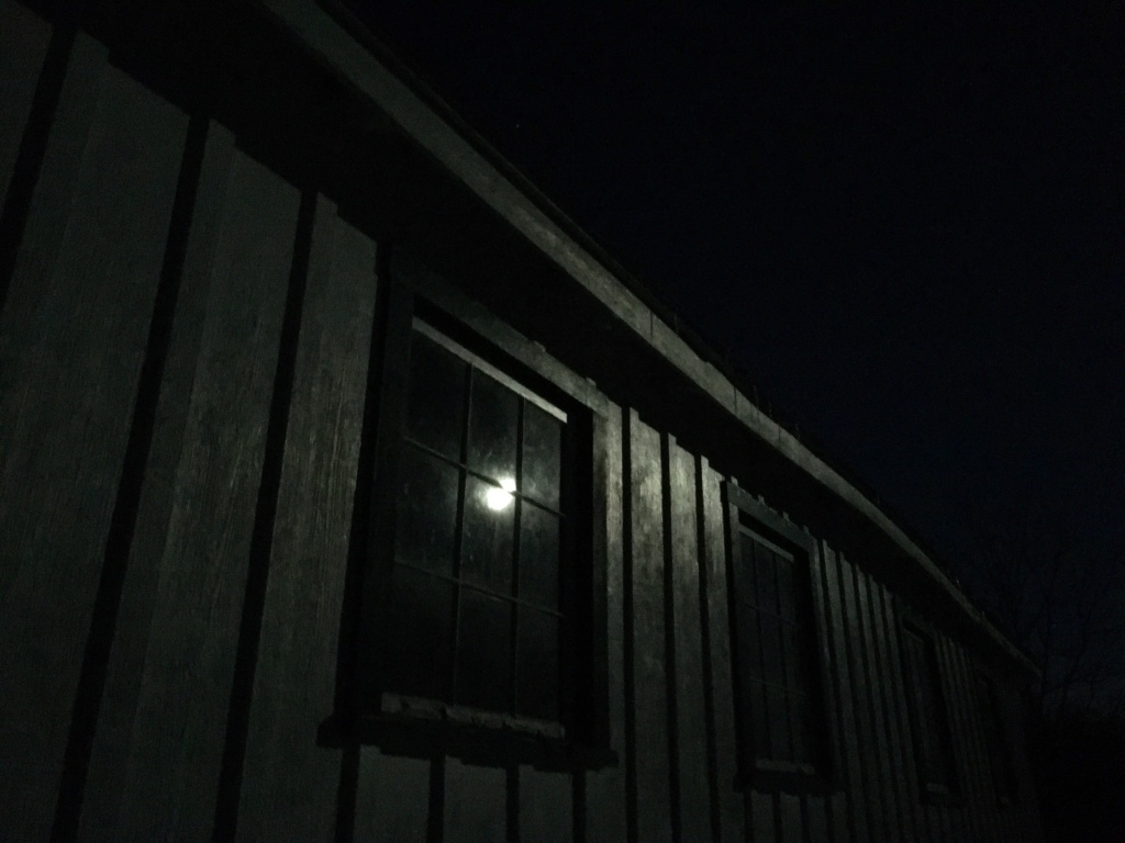 full moon reflected in a window pane