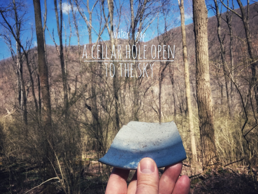hand holding up a blue-and-white-glazed shard of pottery against a background of bare trees and a mountain outlined against the blue sky